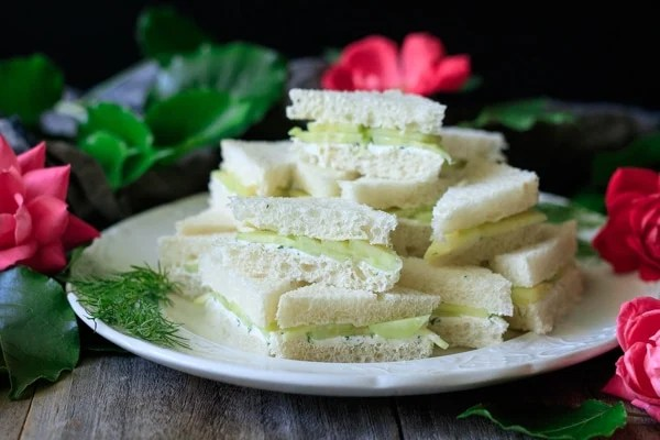 Cucumber sandwiches on a white plate with pink roses