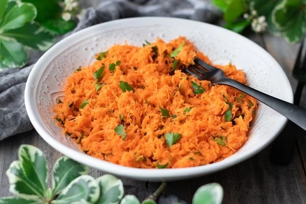white bowl of French grated carrot salad with black fork