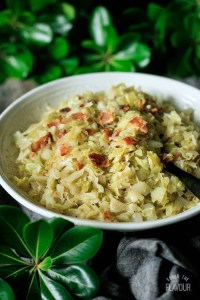 white bowl of Southern fried cabbage with bacon with greenery and gray fabric
