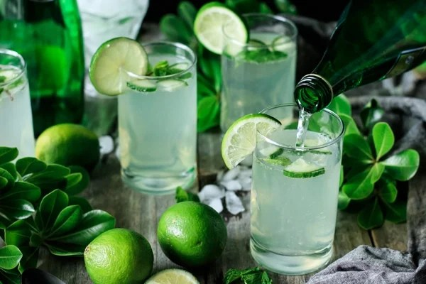 three glasses of lime and mint refresher with fresh limes and greenery