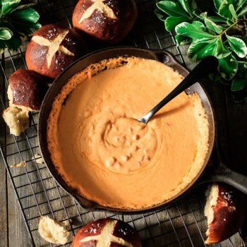 cast iron skillet of pimento cheese dip with a spoon, pretzel buns, and greenery
