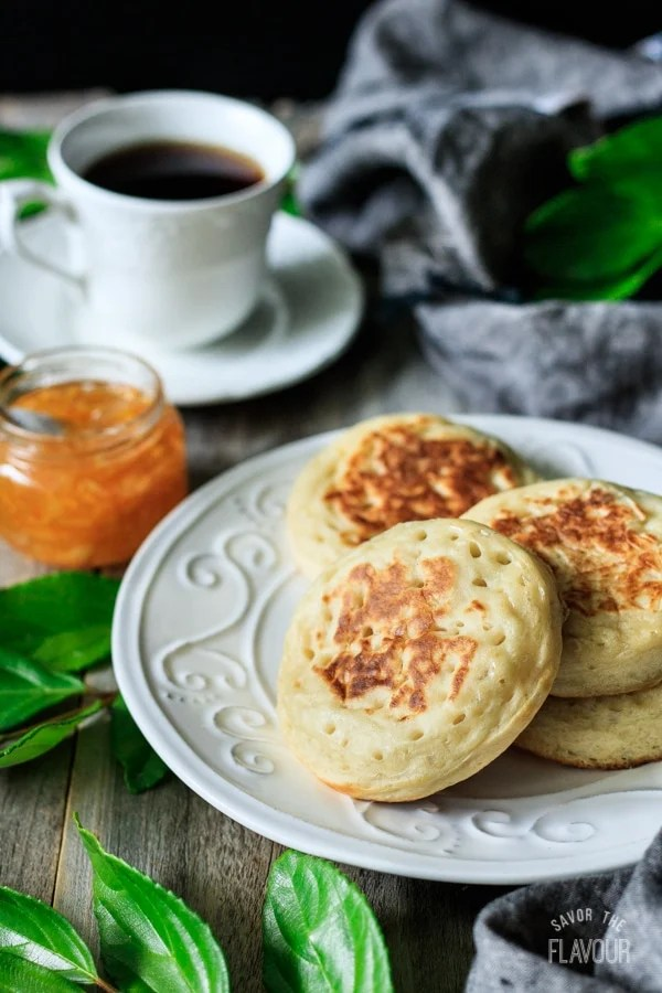 plate of English crumpets with a cup of tea and jar of marmalade