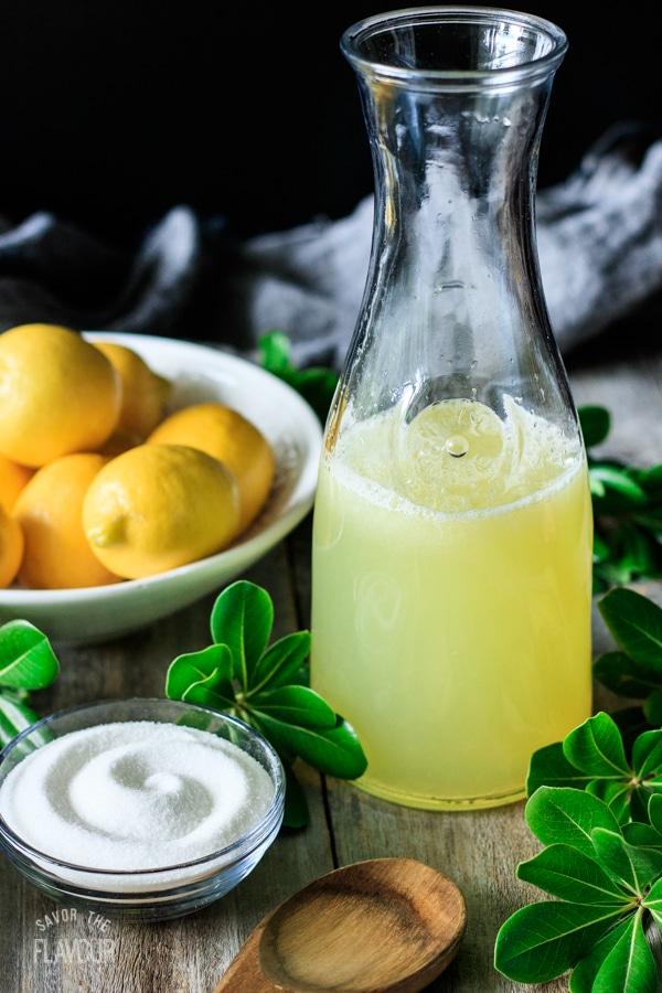 jug of lemonade with sugar and lemons to make frozen lemonade