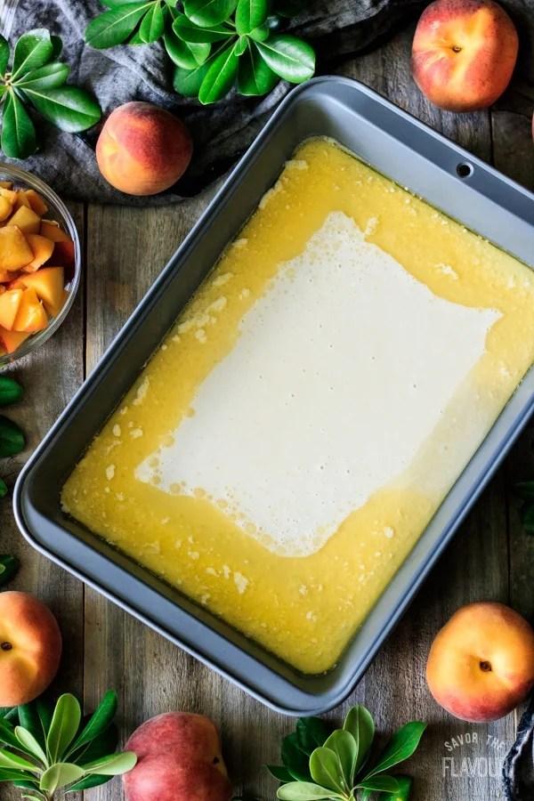peach cobbler batter in pan