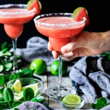 holding a glass of non alcoholic strawberry margarita