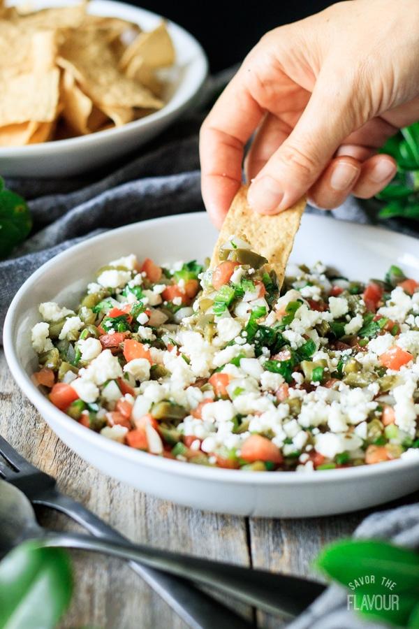 dipping a tortilla chip into cactus salad