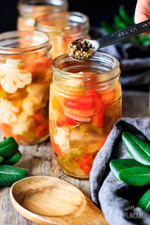 adding spices to a jar of giardiniera