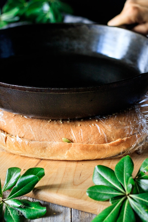 muffaletta sandwich being pressed by a cast iron skillet