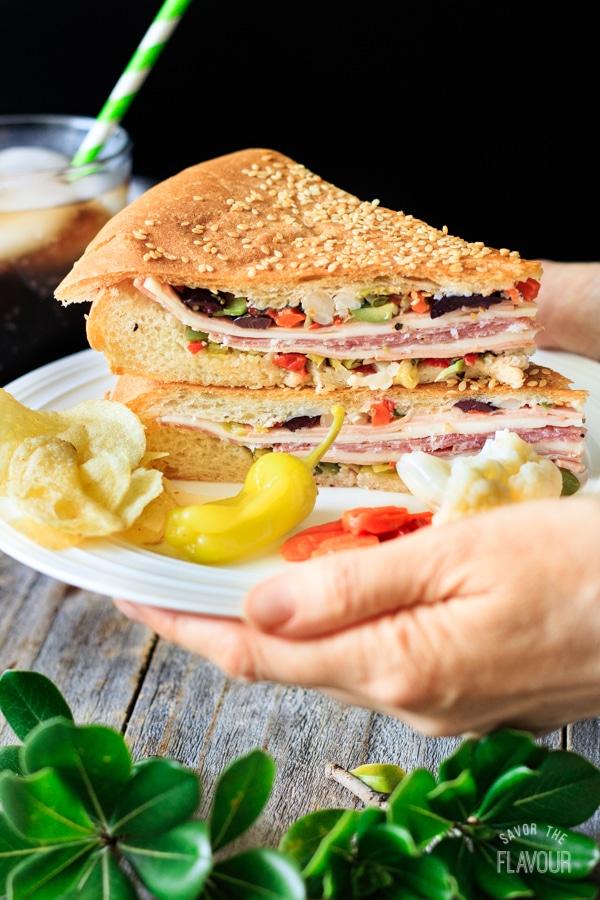 holding a muffaletta sandwich on a plate