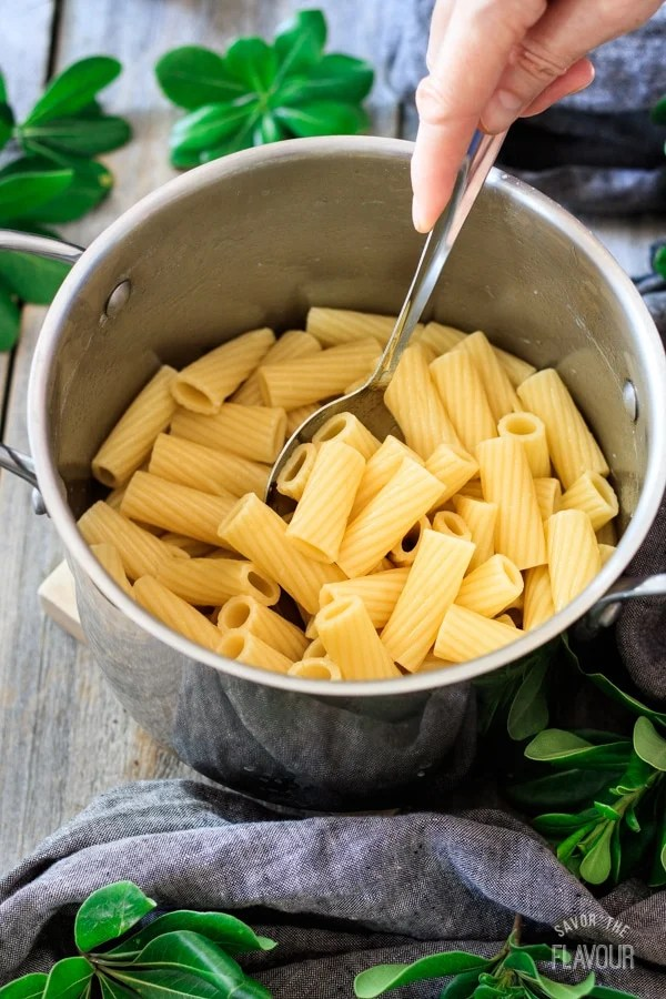 mixing the pasta for sausage, pear, and gouda rigatoni