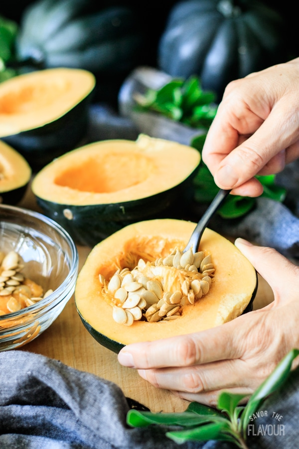 scooping out seeds from an acorn squash