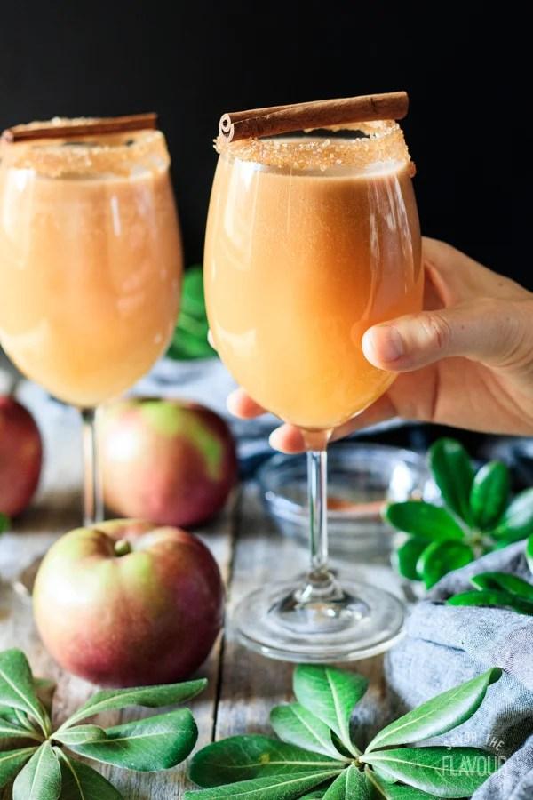 holding a glass of caramel apple mocktail