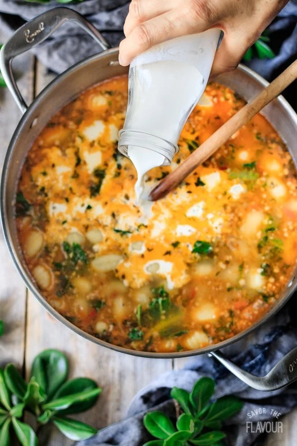 pouring cream into sausage and gnocchi soup