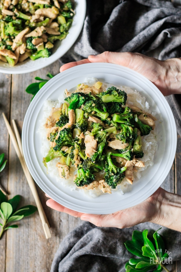 holding a plate of chicken and broccoli stir fry