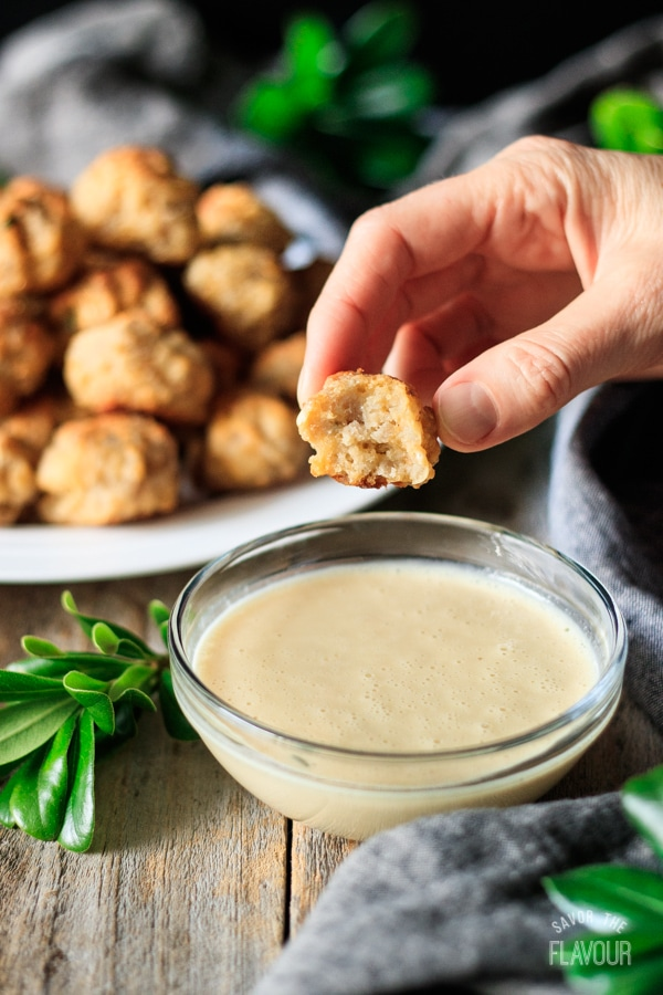 taking a bite of one of the cheesy sausage balls