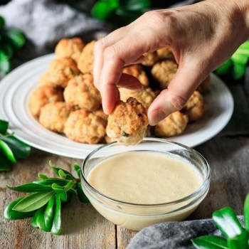 dipping one of the cheesy sausage balls in honey mustard