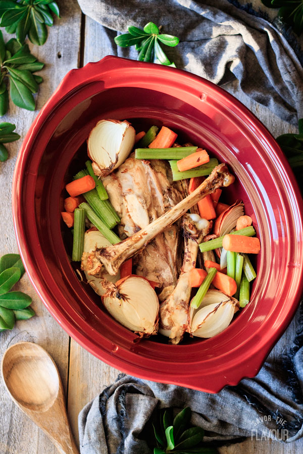 turkey bones and vegetables for roasted turkey stock in crockpot