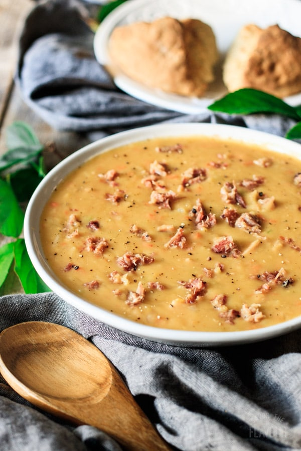 bowl of split pea soup with wooden spoon