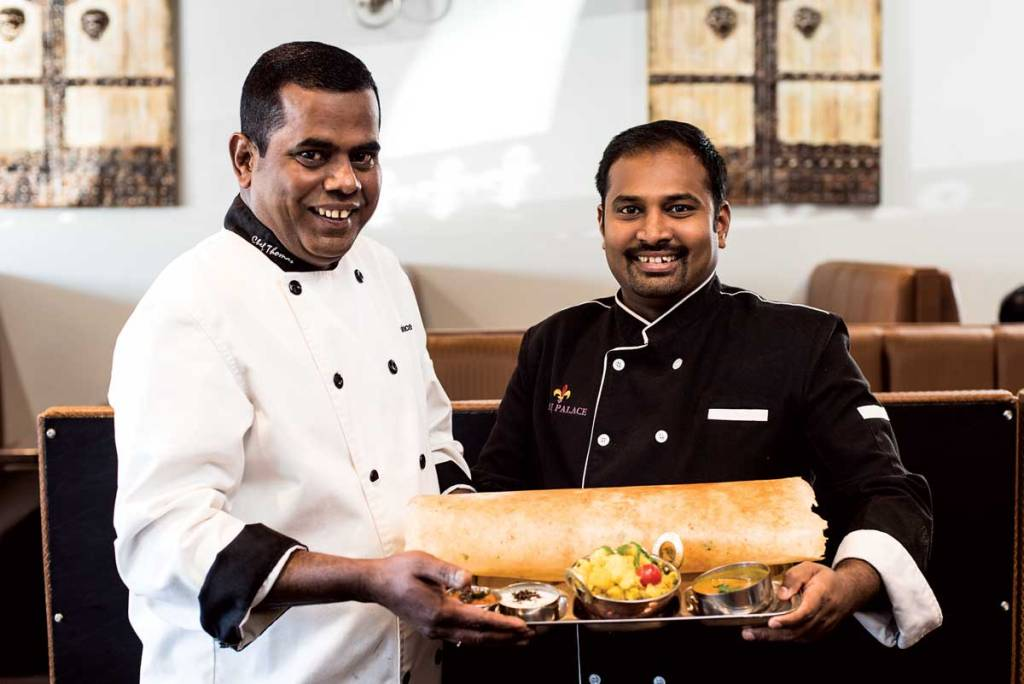 Two Indian chefs with a very large dosa crepe and accompaniments