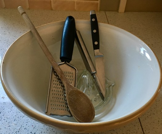 A bowl, wooden spoon, sharp knife, grater all needed to make Christmas pudding