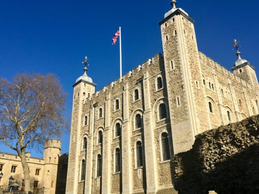 The Union Flag in the clear blue sky, flies over the White Tower at the Tower of London