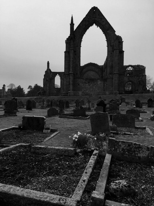 A black and white dramatic image of the ruins of Bolton Abbey