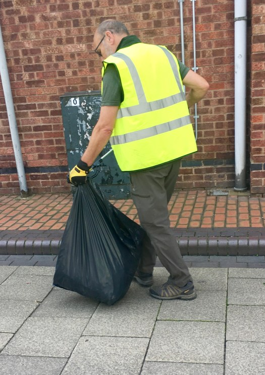 A member of Liam's team cleaning up the town