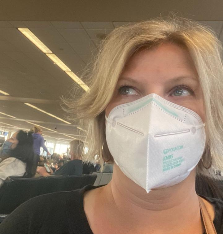Amy with a mask on at the airport traveling for work
