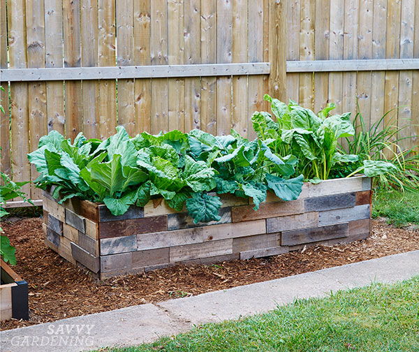 """Old strips of wood in varying shades have been applied to the sides of a standard raised bed frame to create a basic """"mosaic"""" pattern."""