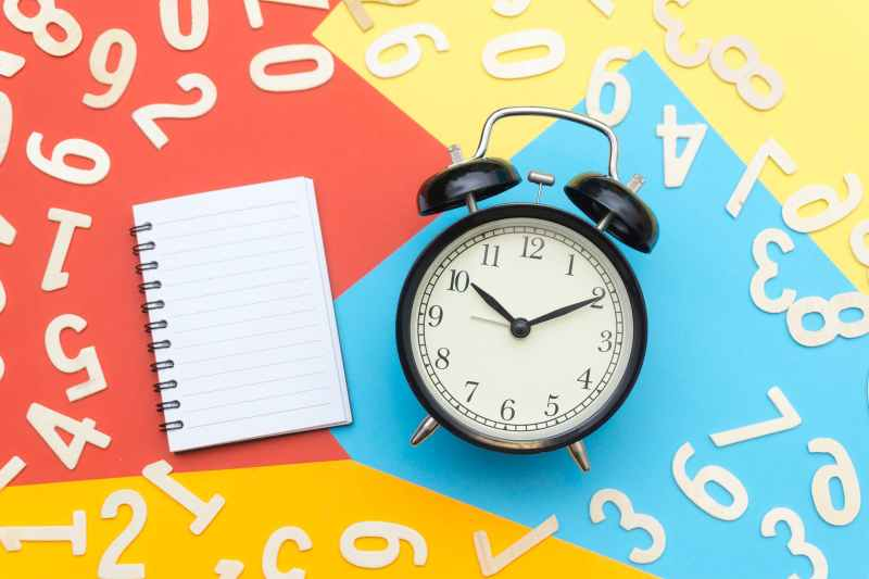 alarm clock lying on multicolored surface