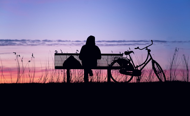 silhouette image of a man sitting in a bench