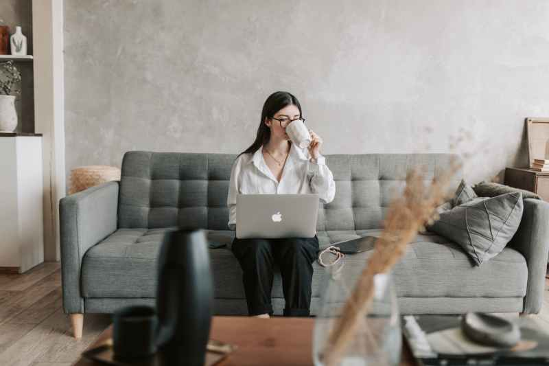 woman drinking coffee while working with laptop