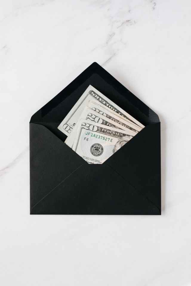black envelope with cash dollars on marble table