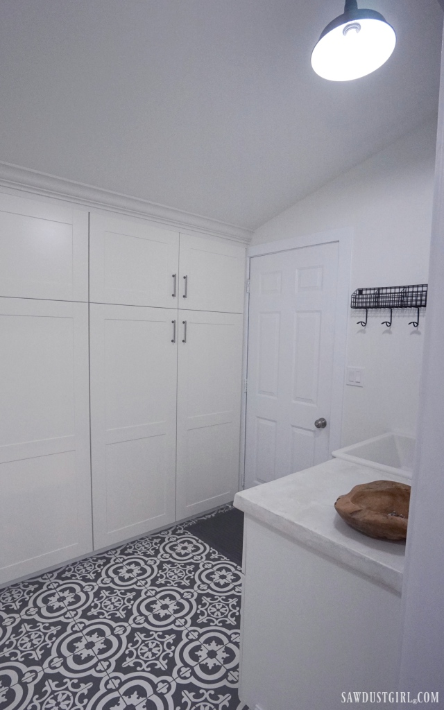 laundry room, black and white tile floor, white cabinets