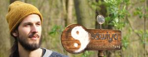 Logo mit Portrait von Coach und Heiler Sven Sebastian Horner, sitzend im Wald mit senfgelber Mütze.
