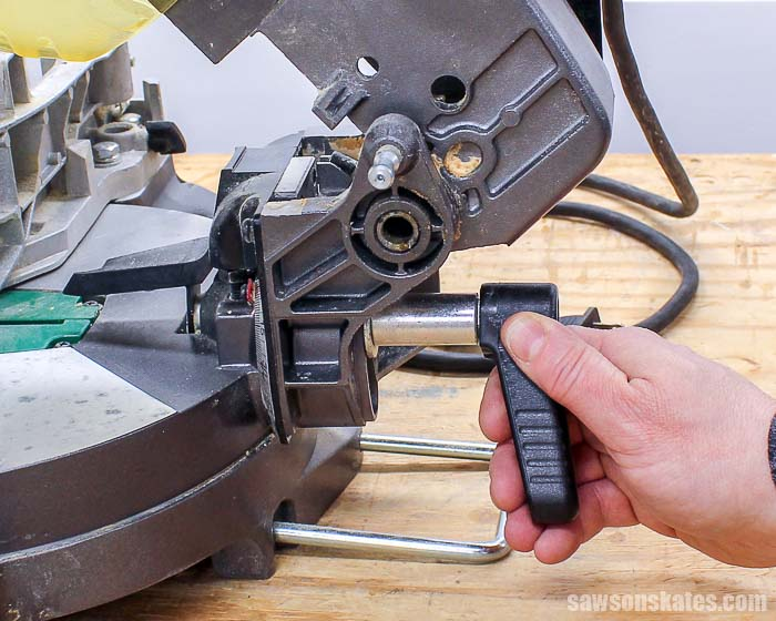 Loosening the bevel handle to adjust the miter saw blade
