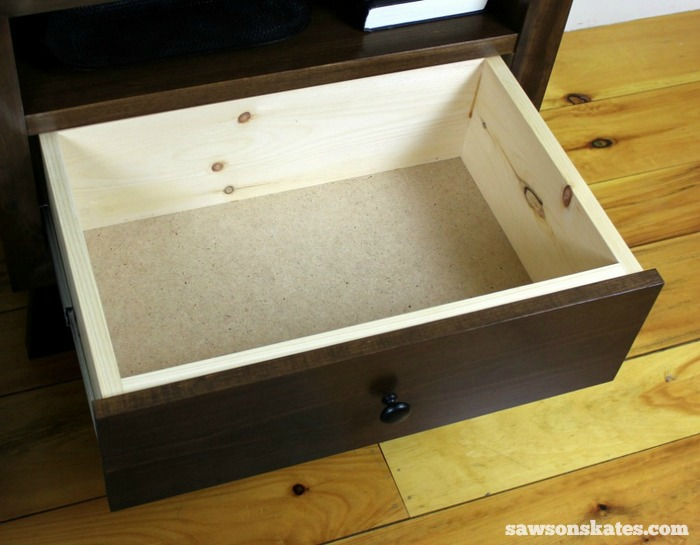 There's more storage in the deep drawer below the shelf. The bottom of the drawer is made of hardboard and the only part of the chunky retro nightstand that isn't made of solid wood.