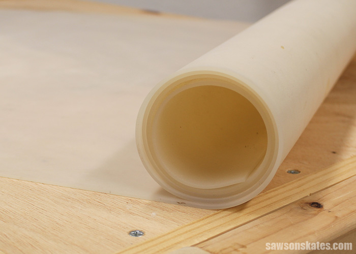 Silicone workbench mat being unrolled to use on workbench