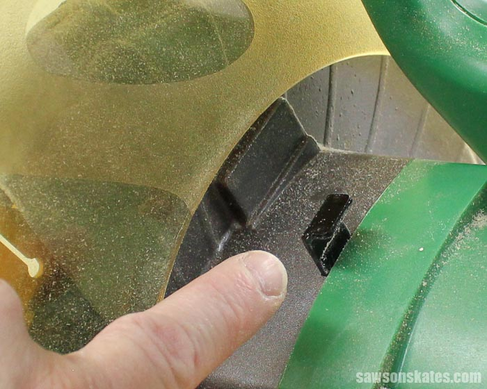 The second step to replacing a miter saw blade is to locate and press the spindle lock