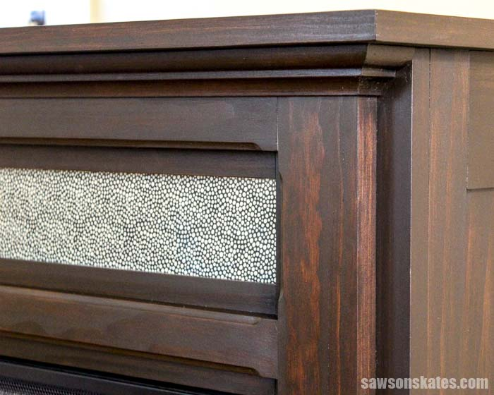A piece of glass in this DIY electric fireplace mantel hides TV cable boxes