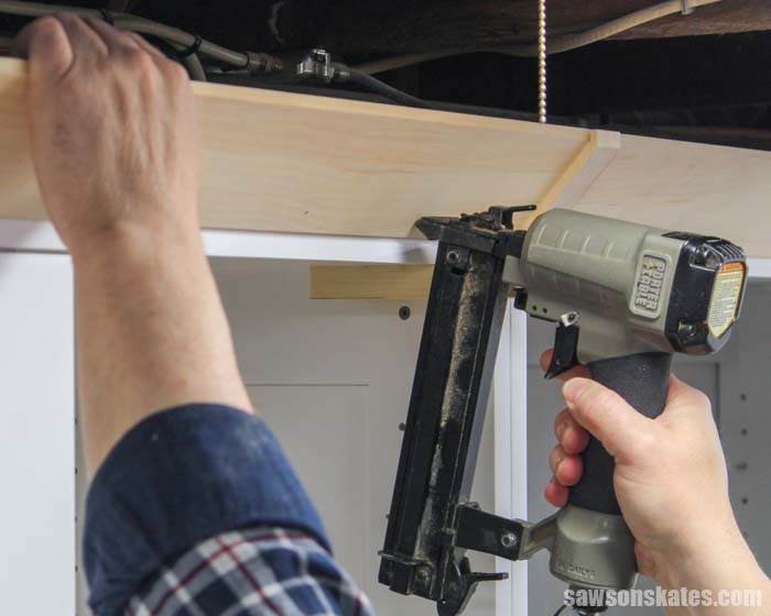 Using a nail gun to install Shaker style crown molding that was made with a table saw