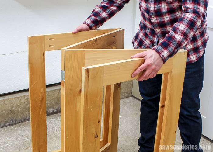 Closing the legs of the DIY collapsible workbench.