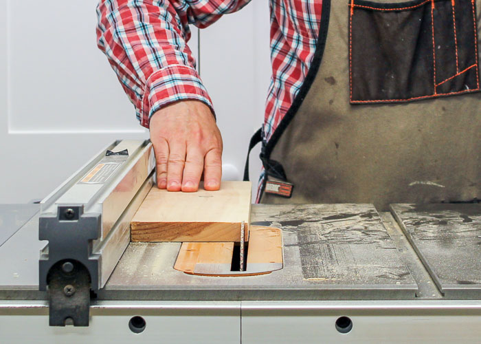 Using a table saw to rip a piece of wood to width