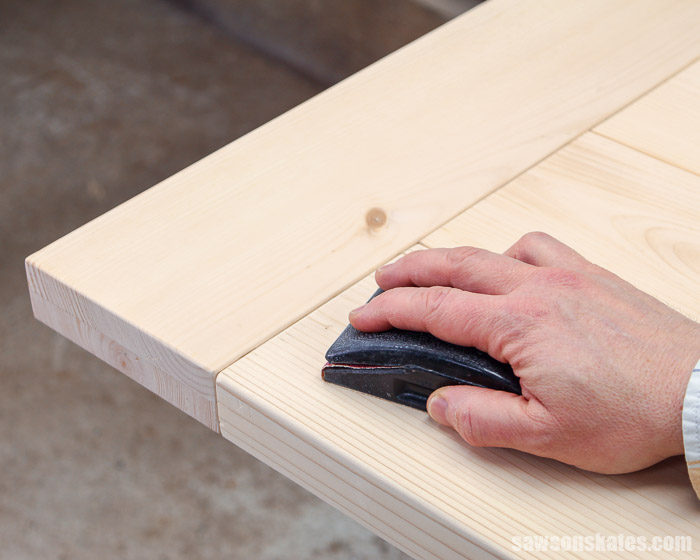 Using a sanding block on a DIY farmhouse table top with breadboard ends