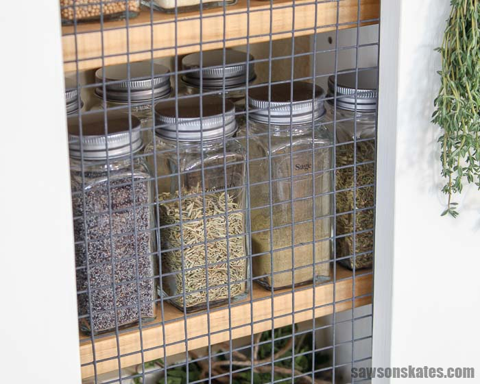 Spice jars lined up in an easy to build DIY spice rack