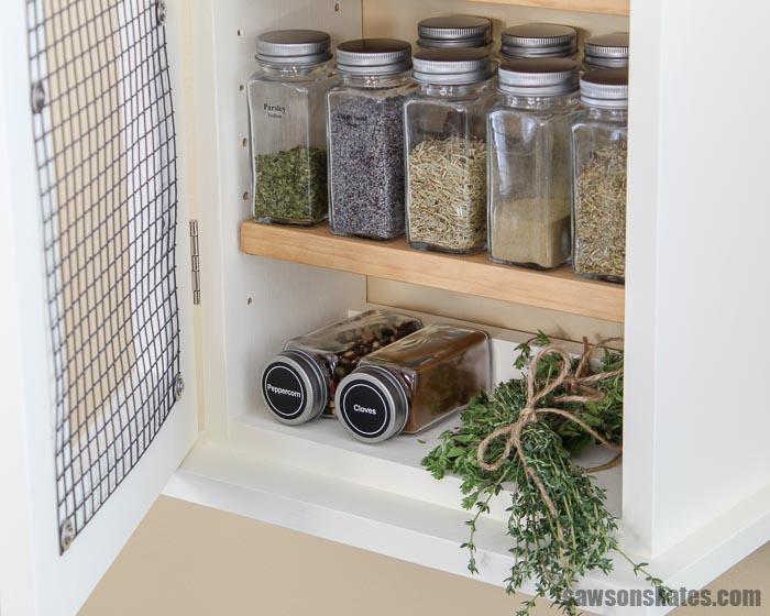 Herbs and spices organized in a wall-mounted DIY spice rack