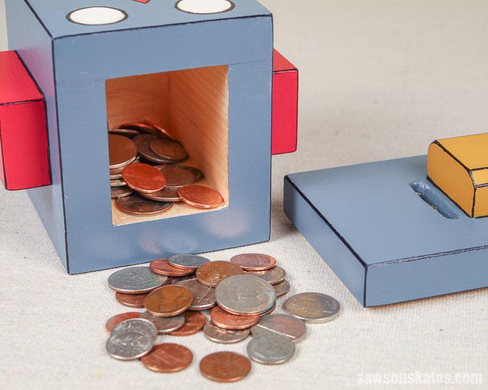 Coins spilling out of a cute robot-shaped DIY piggy bank