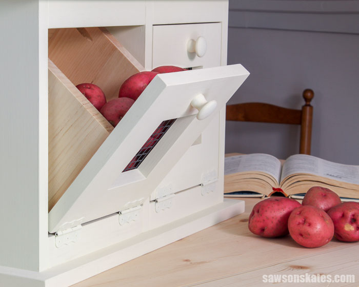 A farmhouse DIY vegetable storage bin with a tilt out drawer filled with potatoes