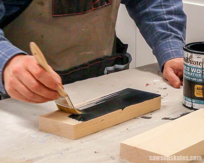 Using a paintbrush to apply a charred wood accelerator to a piece of pine