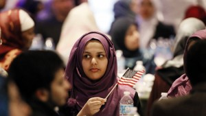A young woman waves an American flag along with others at the beginning of a January 2015 Muslim conference against terror and hate in Texas.